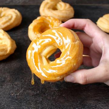 Honey Lemon Glazed Cruller Donut held in a hand