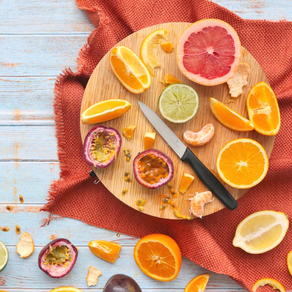 Fresh sliced Citrus Fruits and Passon Fruit on a round cutting board over an orange napkin