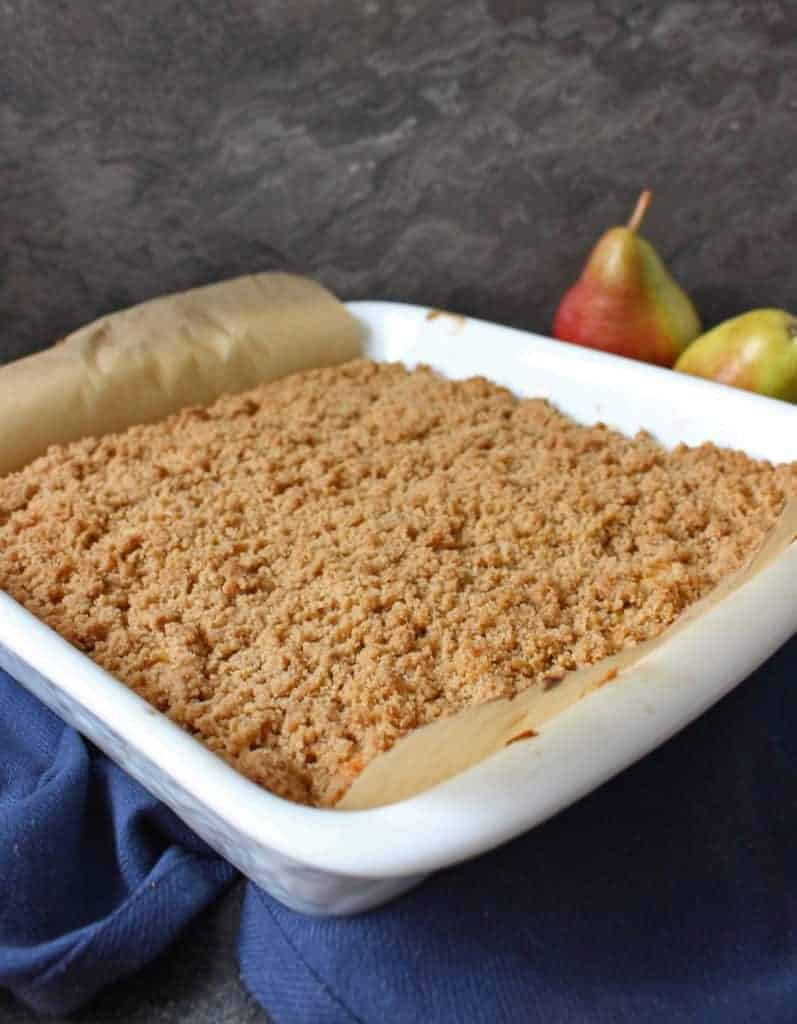 Pear Crumble Cake in a white ceramic dish over a navy napkin.