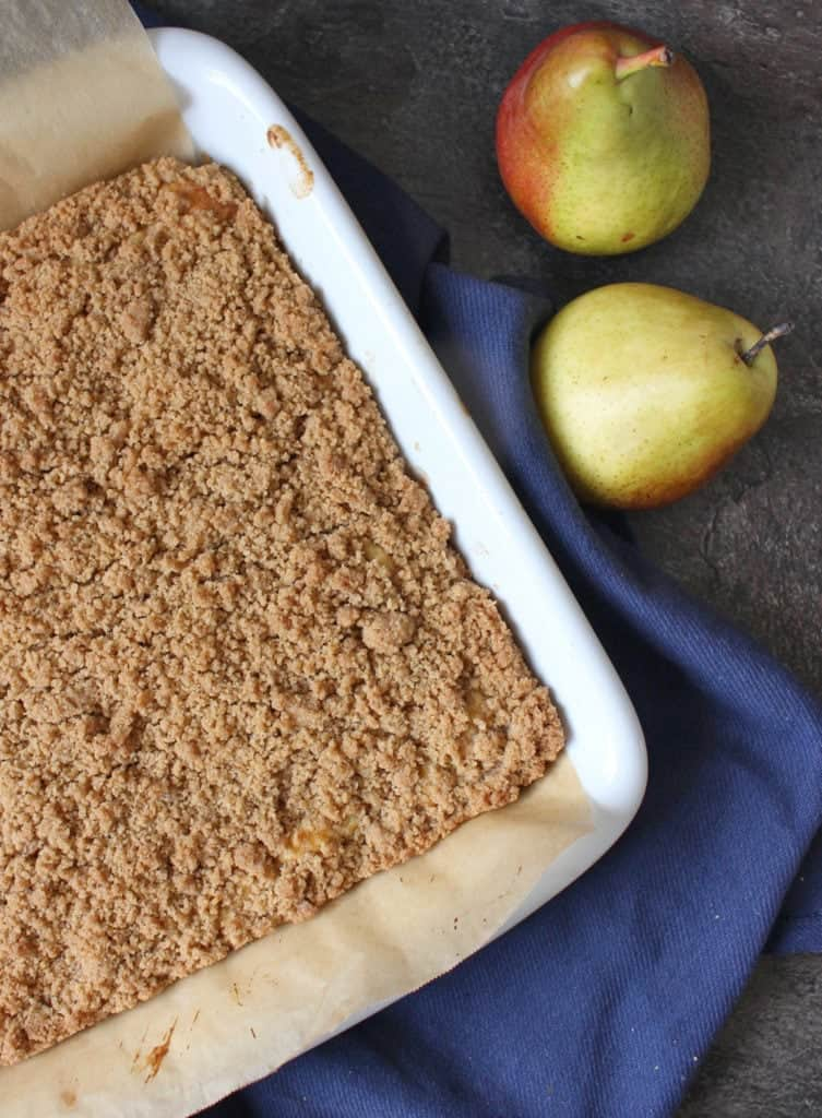 Crumble Cake from above next to two fresh pears.
