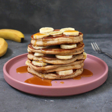 Stack of Buckwheat Banana Pancakes on a pink plate with maple syrup