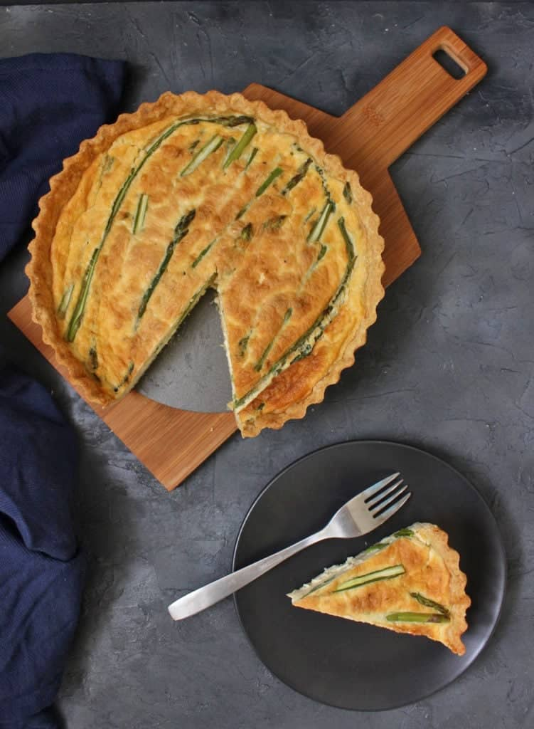 Flatlay photo of the quiche on a wooden board and a slice on a black plate