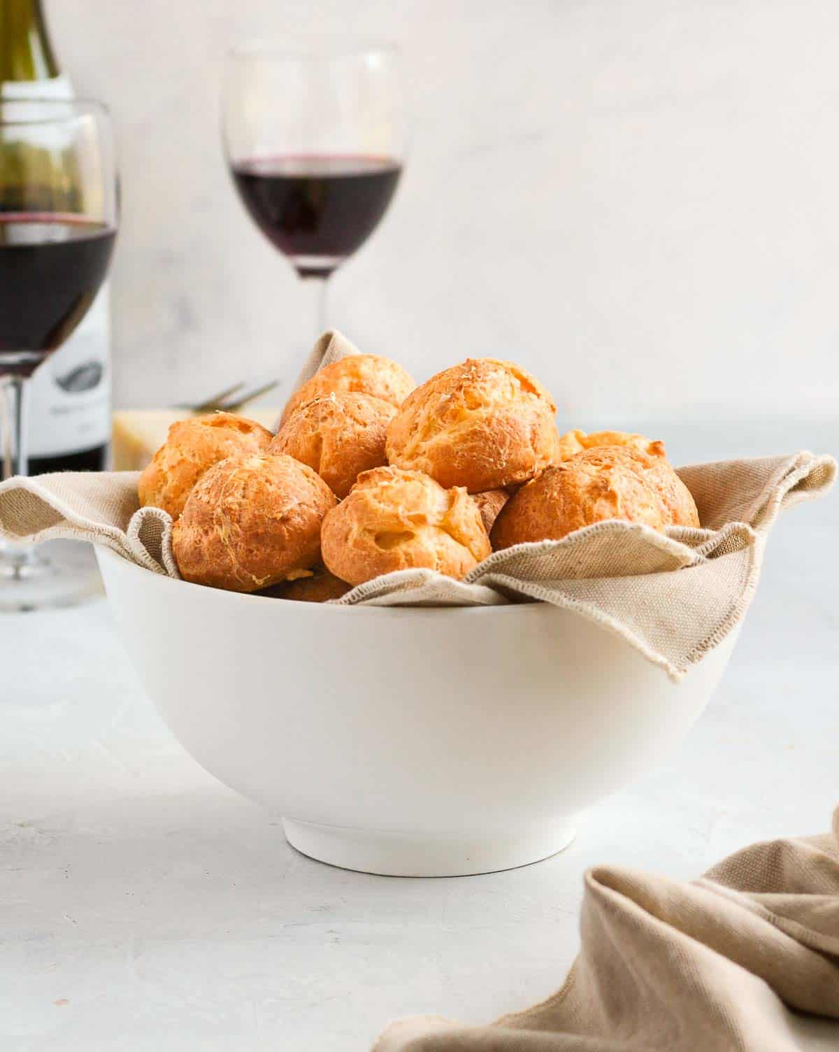 Gougeres in a white bowl with wine glasses in the background.