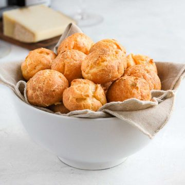 Cheese puffs in a white bowl over a beige napkin.