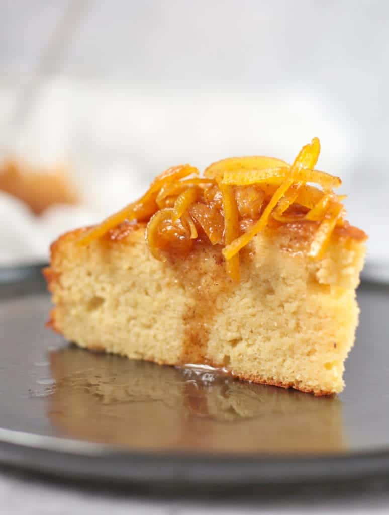 Close up on a slice of cake topped with the syrup and candied oranges