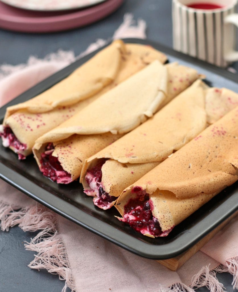 Crepes filled with a berry compote on a black plate.