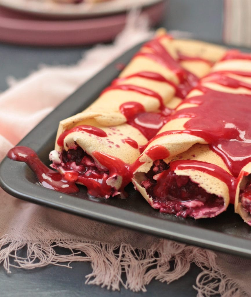 Crepes rolled on a black plate and covered with a Raspberry Coulis.