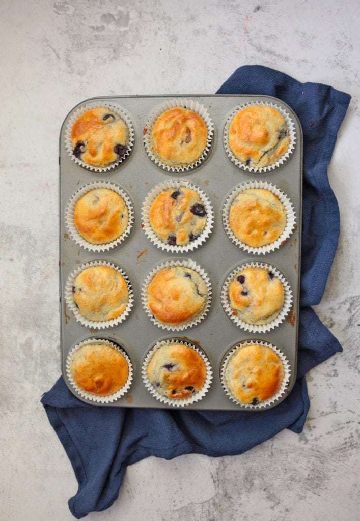 Muffins in the pan over a blue napkin  from above