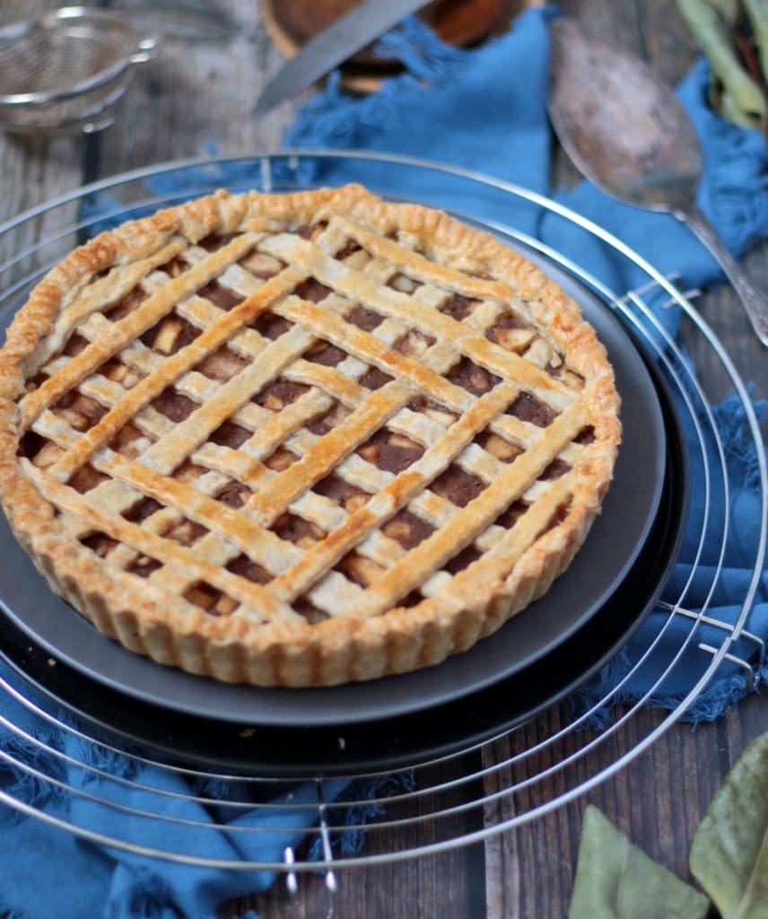 Pear Pie on a grey plate over a round cooling rack.