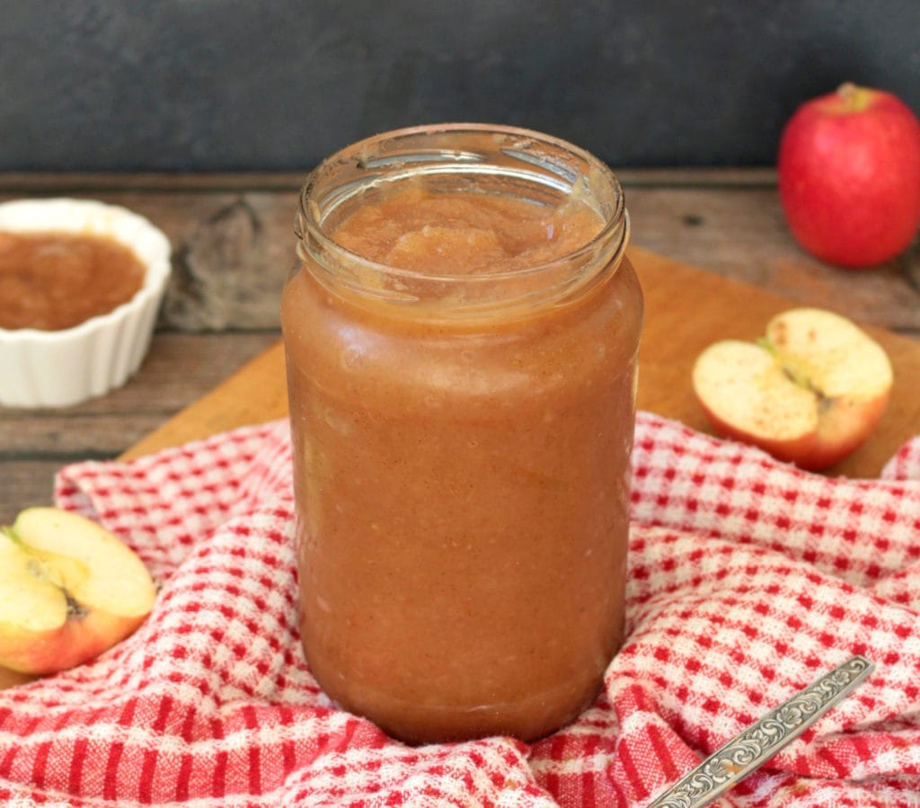 Apple sauce in a glass jar over a red and white tea towel