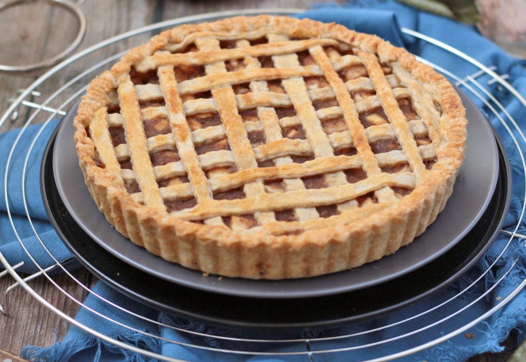 Close up on the pie over a grey plate and a metal cooling rack