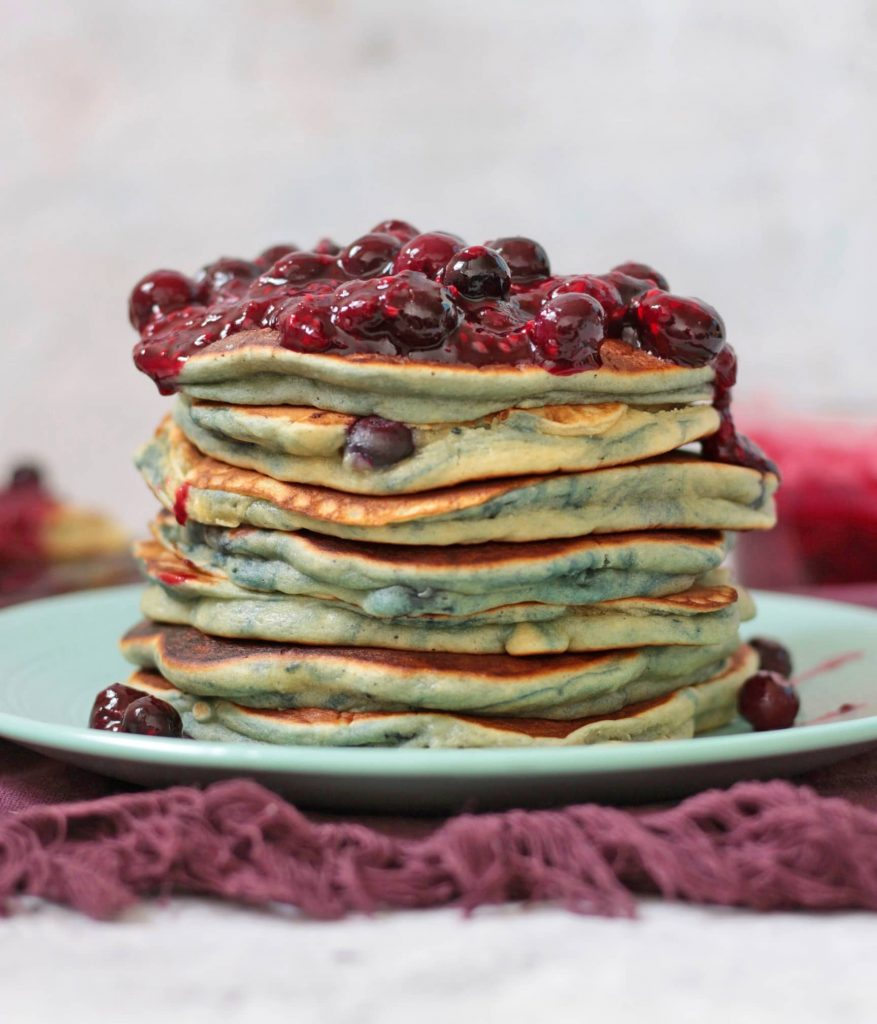 Blueberry Pancake Stack on a green plate over a purple tea towel.