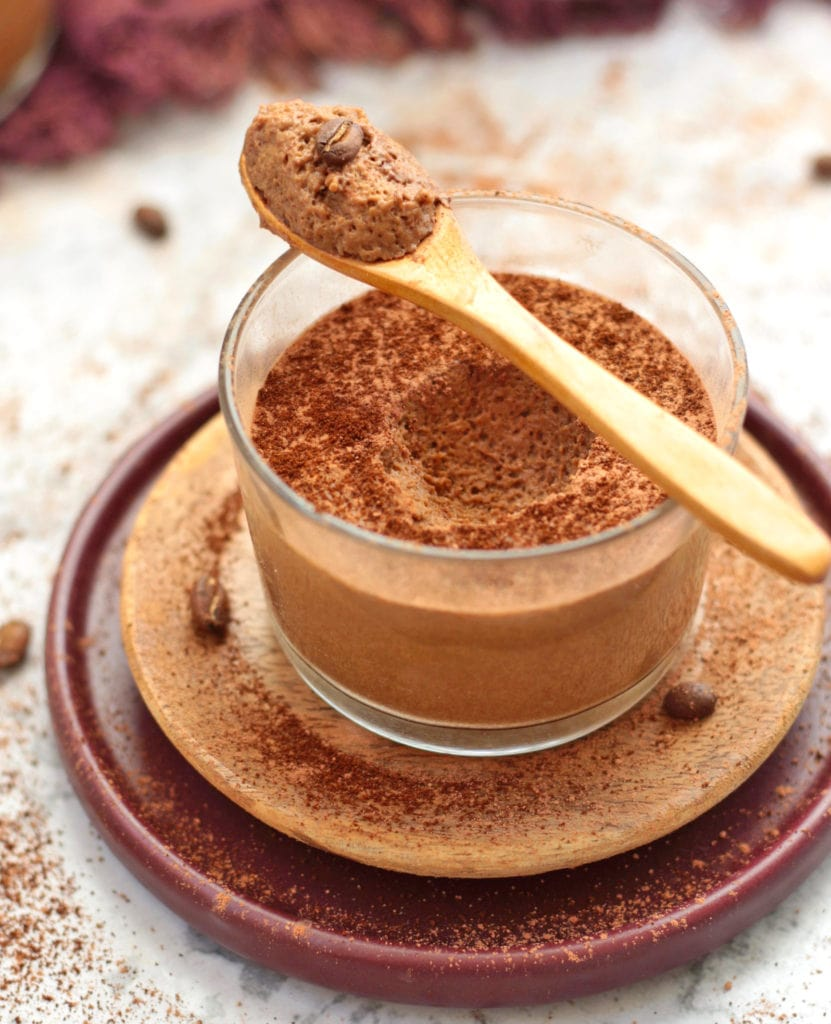A spoon with the Coffee Mousse over the cup