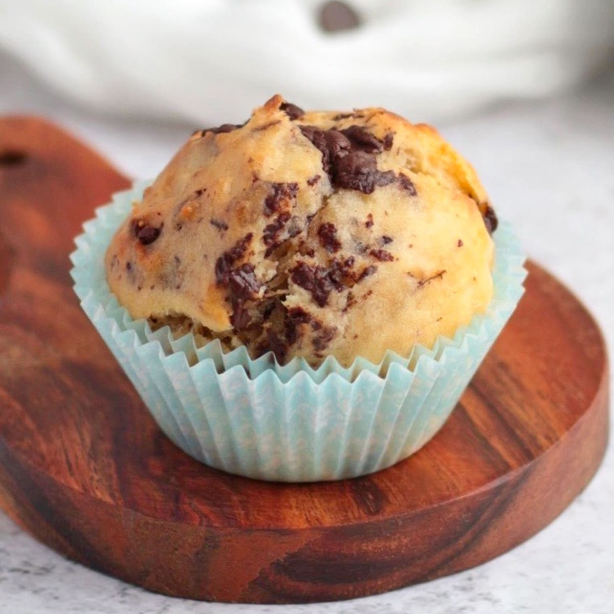 One Chocolate Chip Banana Muffin on a wooden board