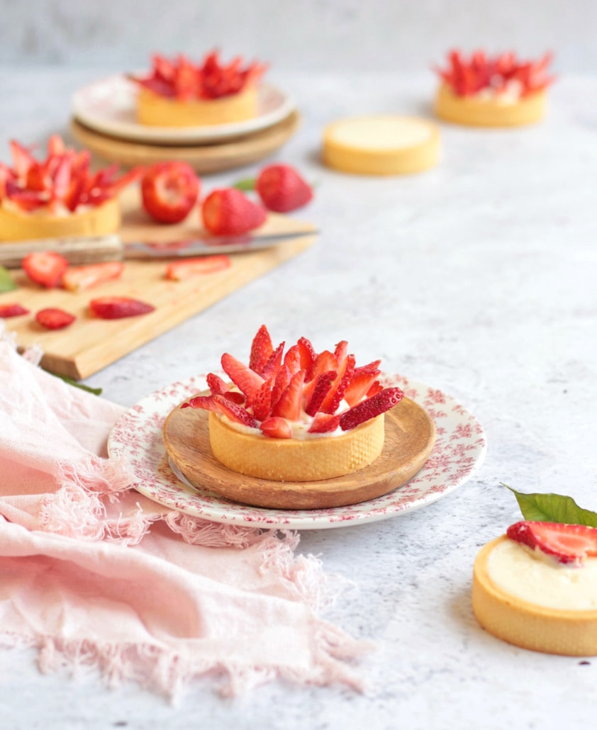 Small Strawberry Tart on a plate with a pink napkin and a wooden cutting board with strawberries in the background