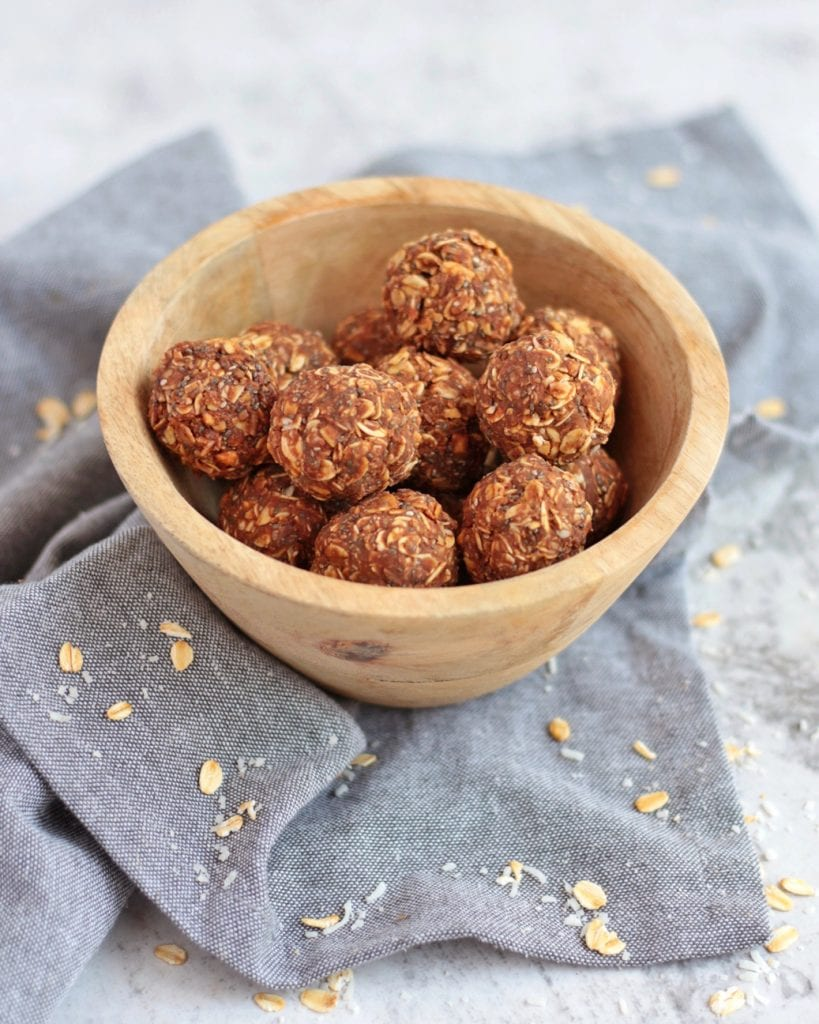 Chocolate Peanut Butter Bliss Balls in a bowl on a grey napkin