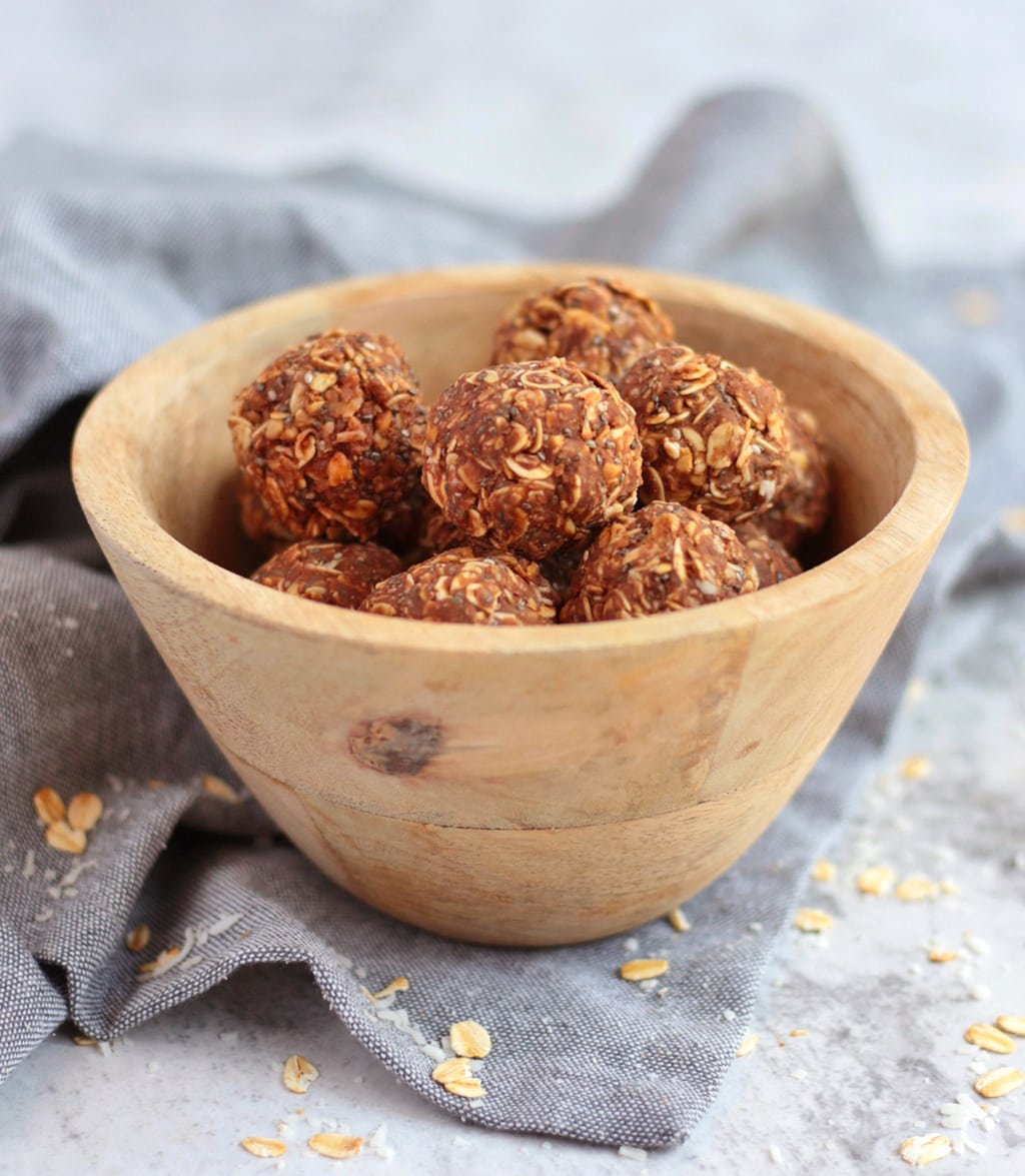Peanut Butter Chocolate Balls in a wooden bowl over a grey napkin.