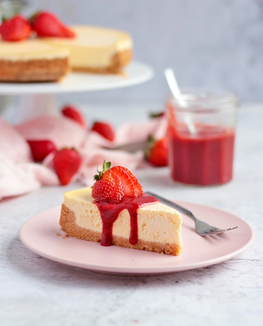 One slice of ricotta cheesecake with strawberry sauce and cheesecake on a cake stand in the background