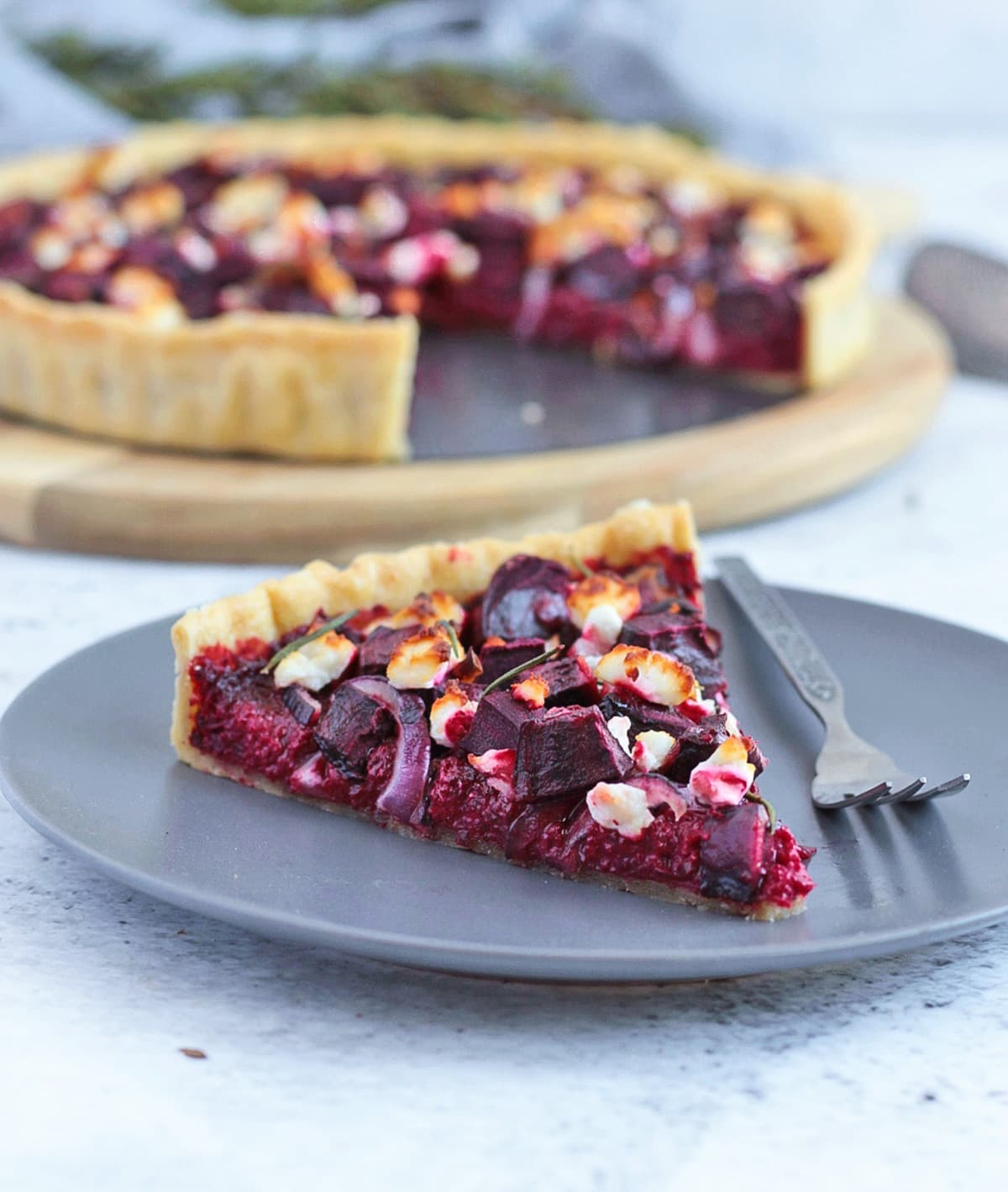 A slice of tart on a grey plate