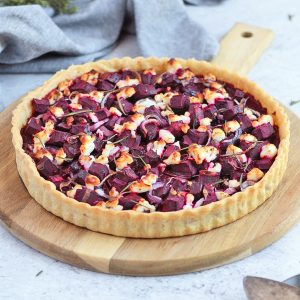 Beetroot and Goats Cheese Tart on a round wooden board