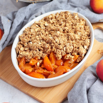 Placing the oat crumble over the fresh apricots