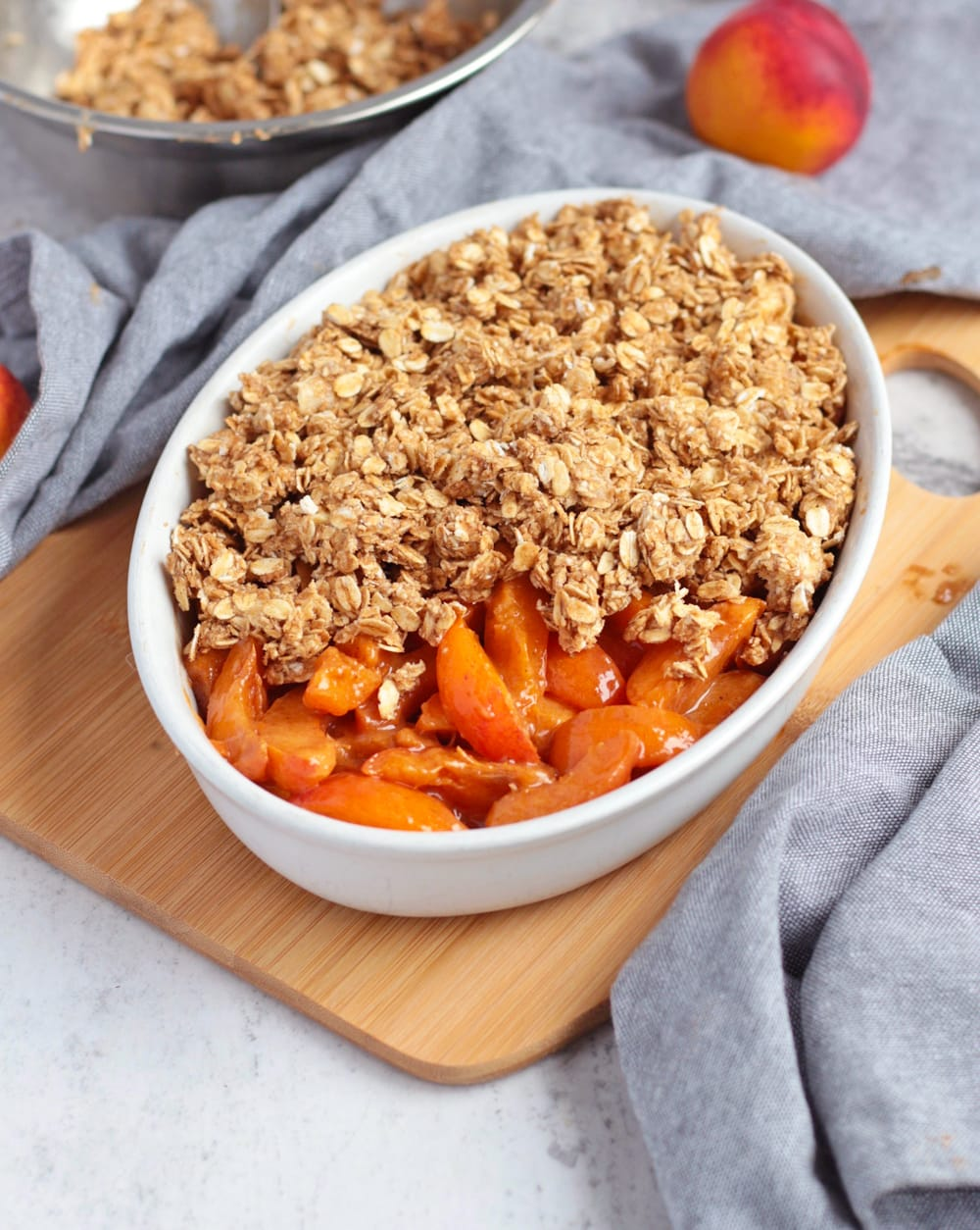 Apricot filling in a ceramic dish half covered by the crumble topping