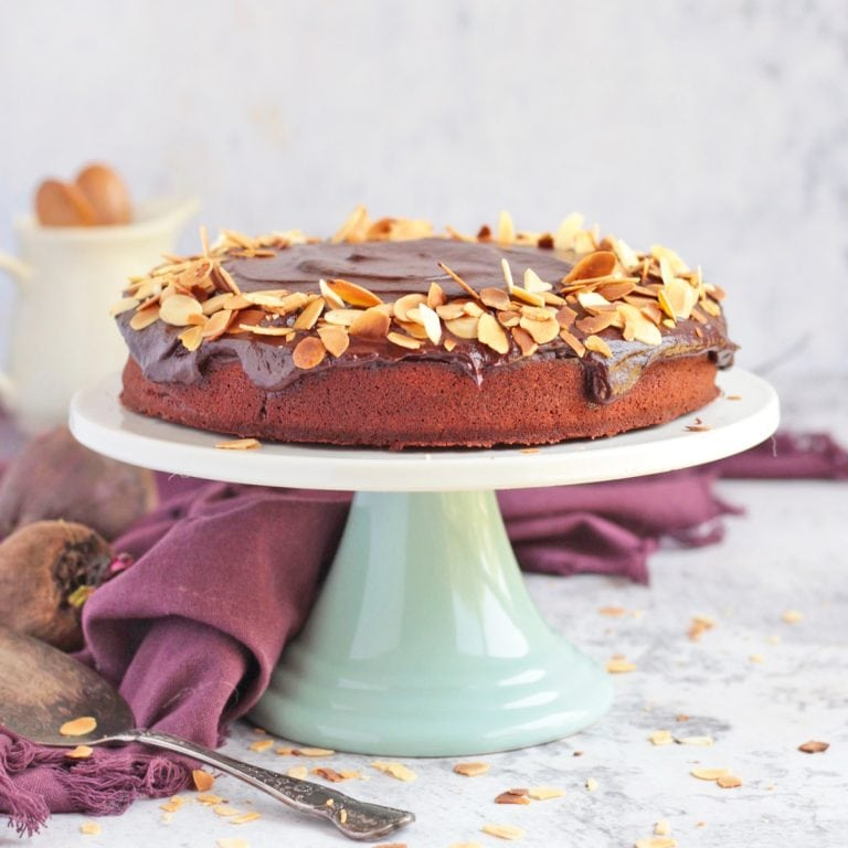 Chocolate Beetroot Cake topped with flaked almonds on a cake stand