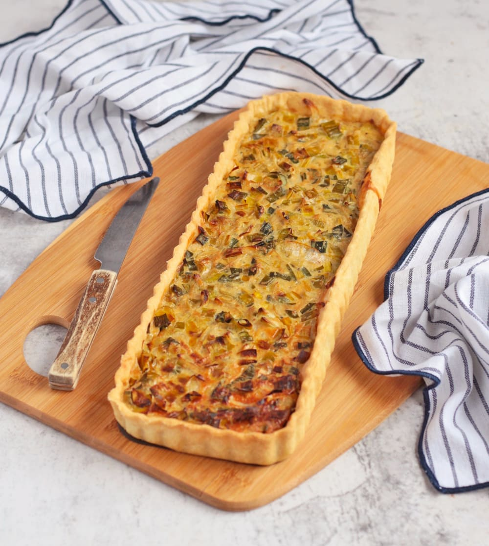 Finished savoury tart on a board with a knife