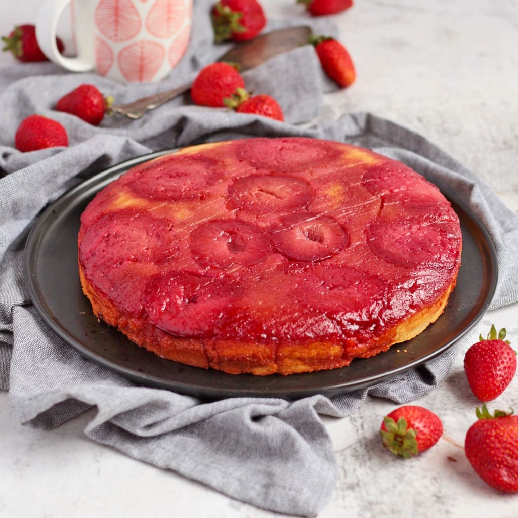 Plum Upside Down Cake on a black plate.