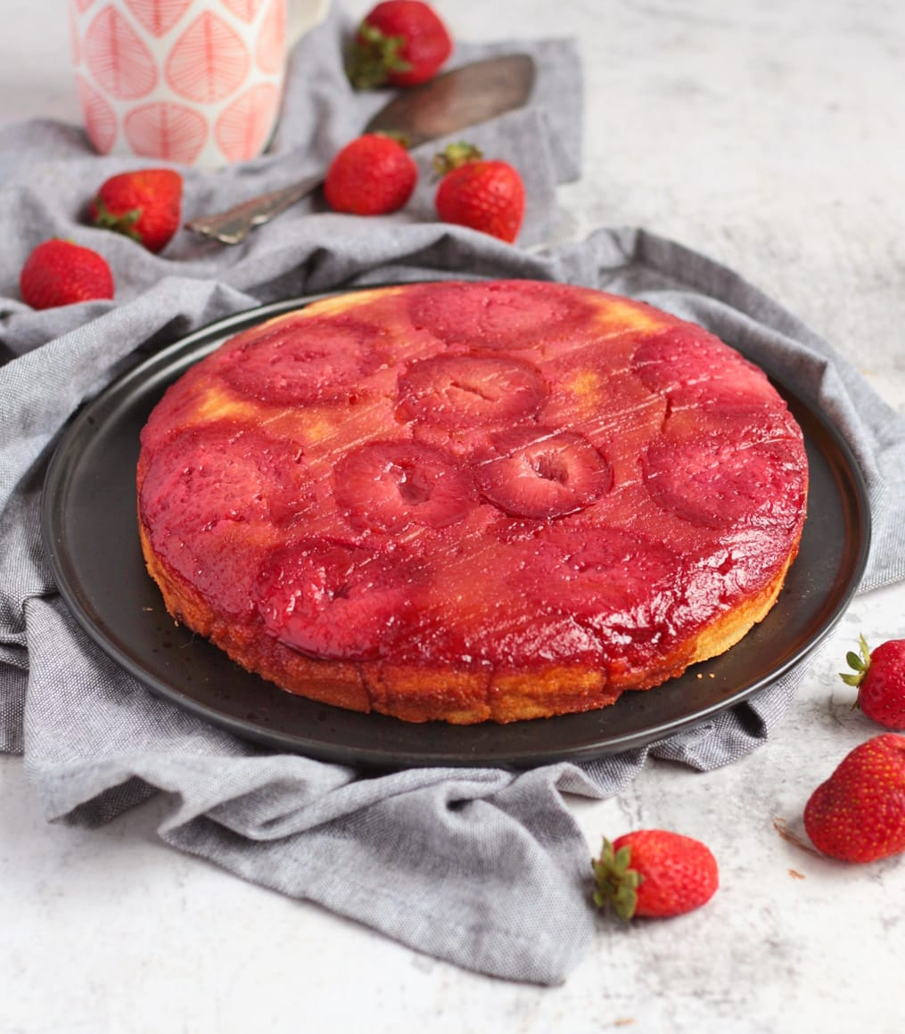 Upside Down Plum Cake on a black plate surrounded by strawberries.