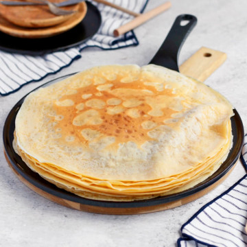 stack of crepe over a black skillet
