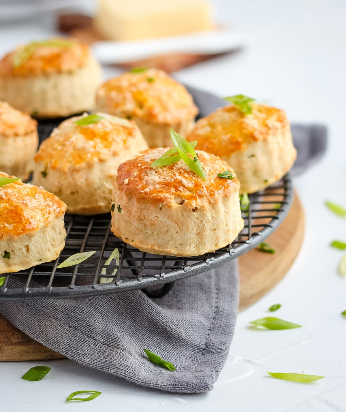 Scones on a round cooling rack over a grey napkin and wooden board