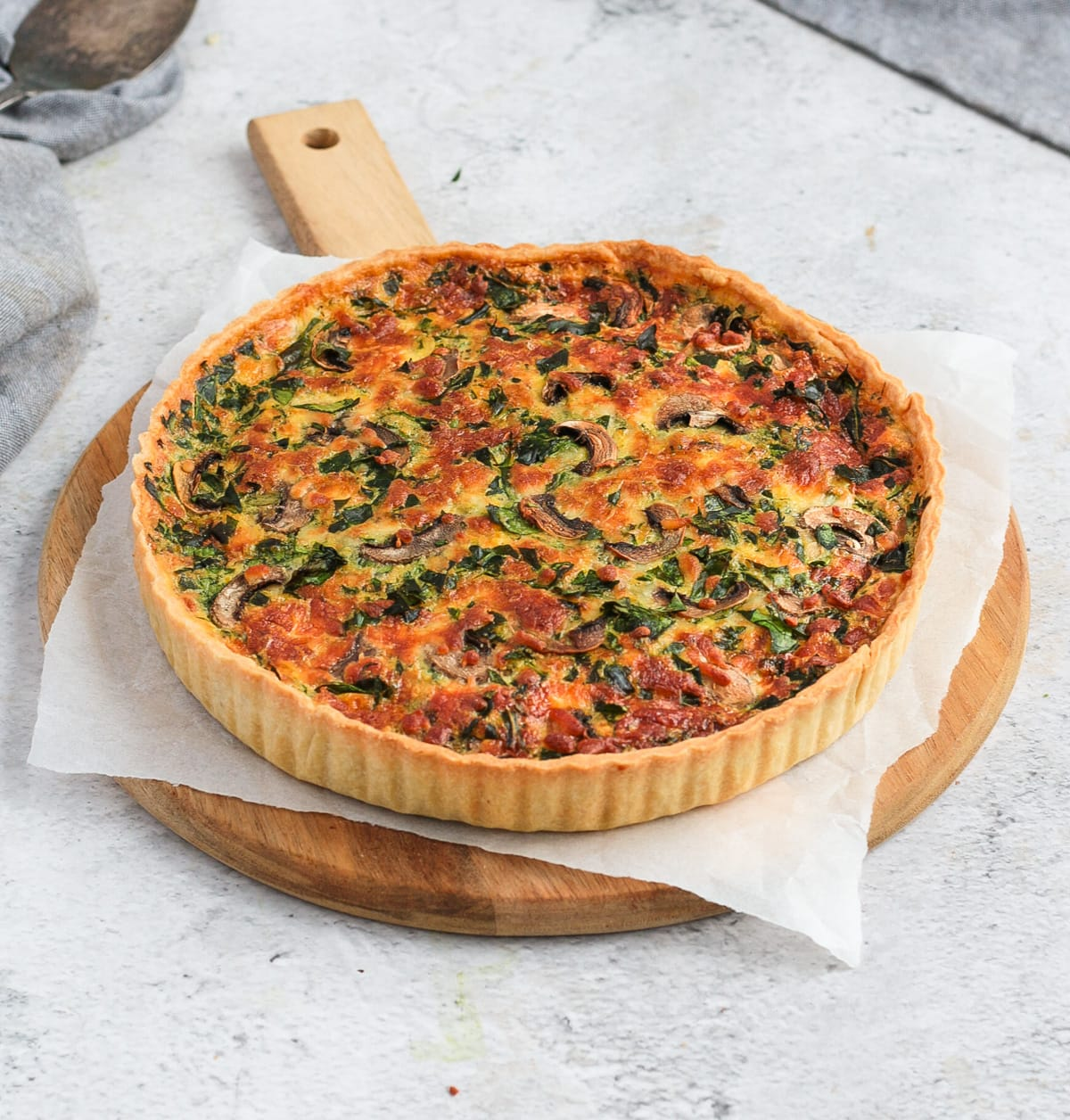 Quiche on a round wooden board over a grey surface