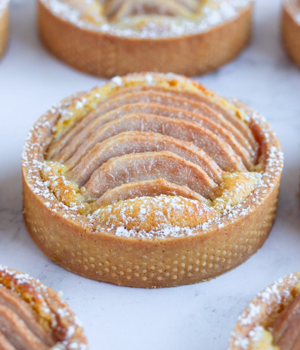 One pear tartlet on a grey surface surrounded by more tarts.