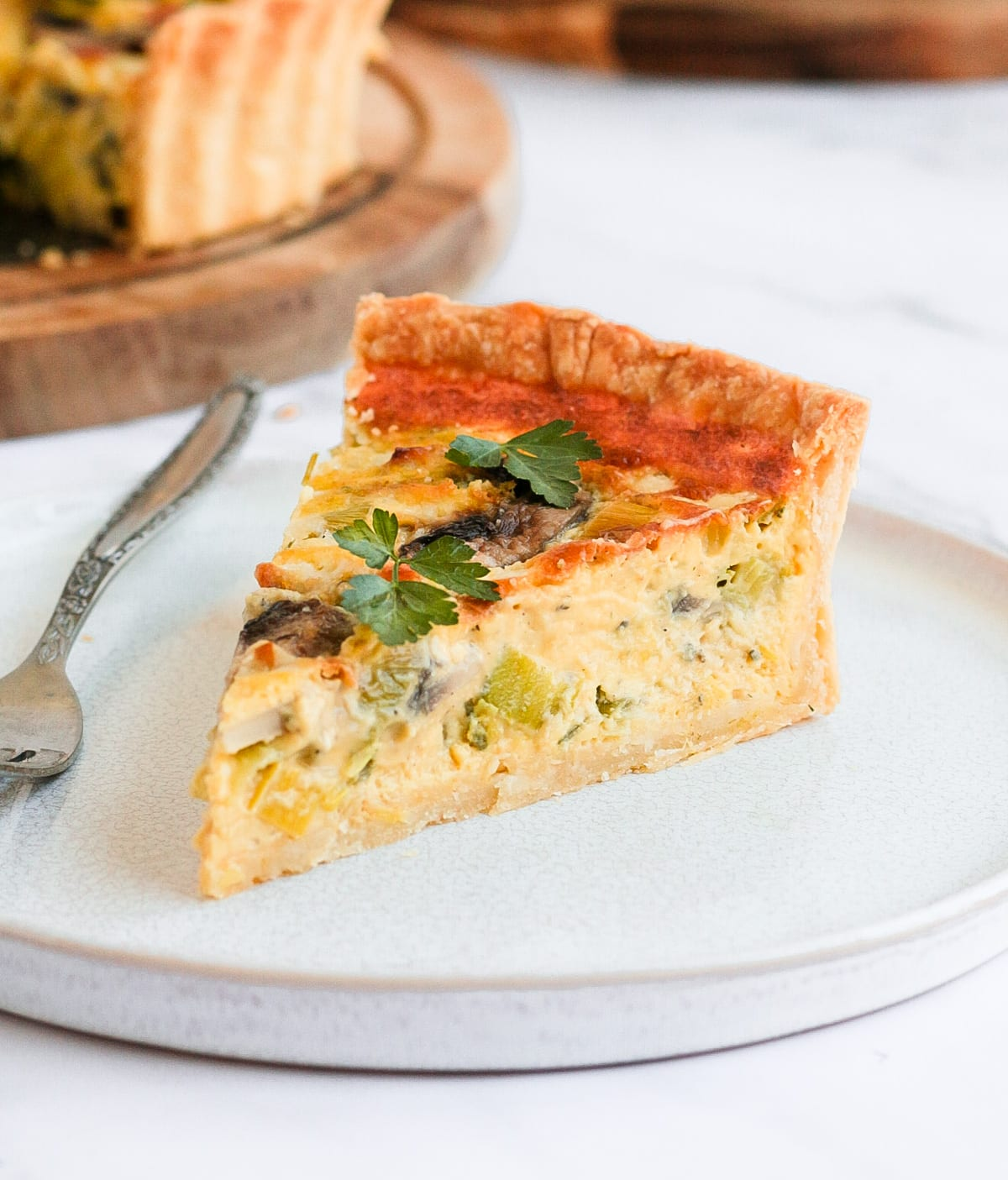 One slice of quiche on a white plate