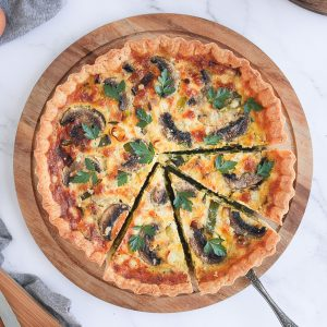 Flatlay photo of the quiche on a round board with 3 slices cut off