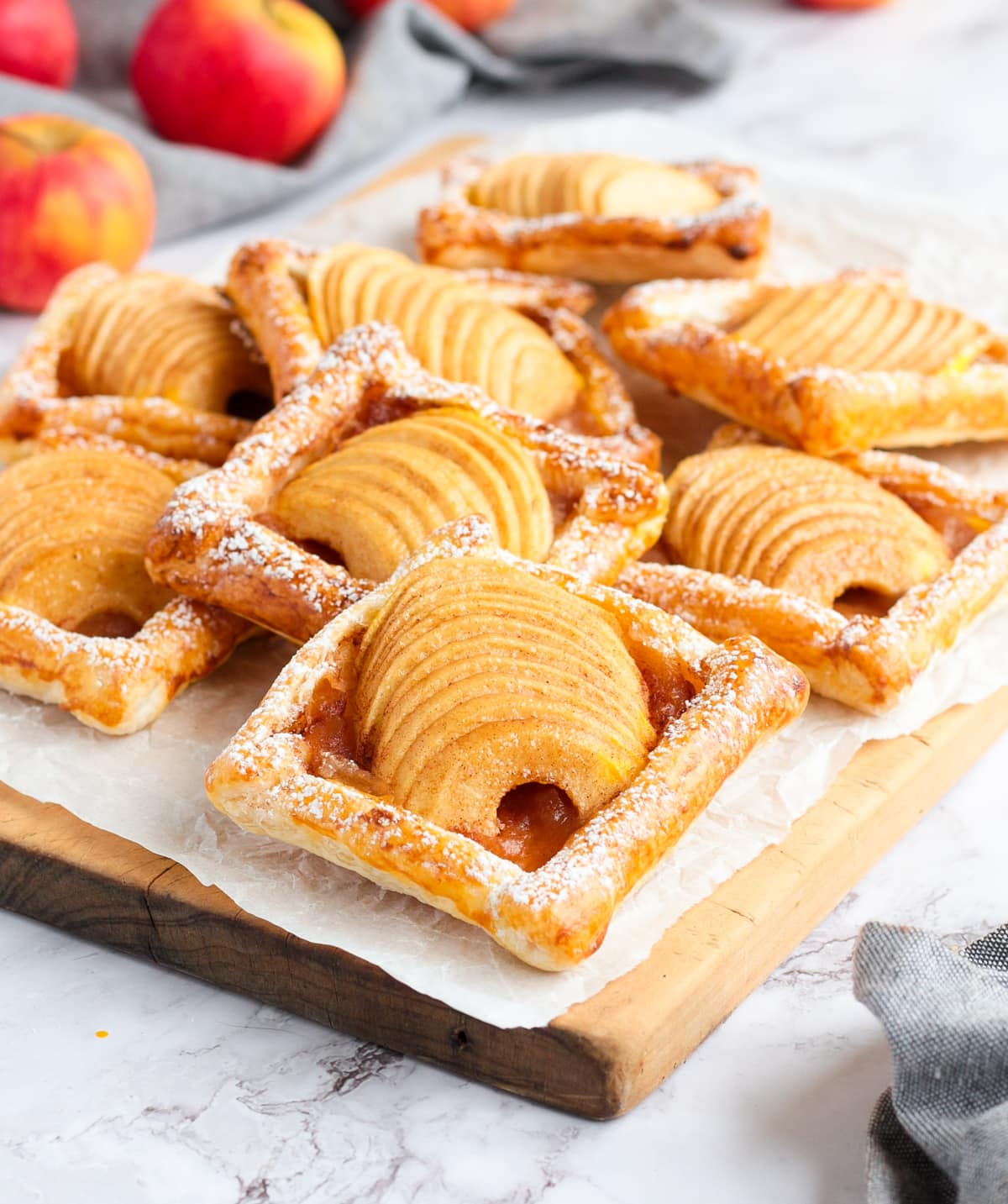 Stack of tarts over a wooden cutting board and a sheet of baking paper.