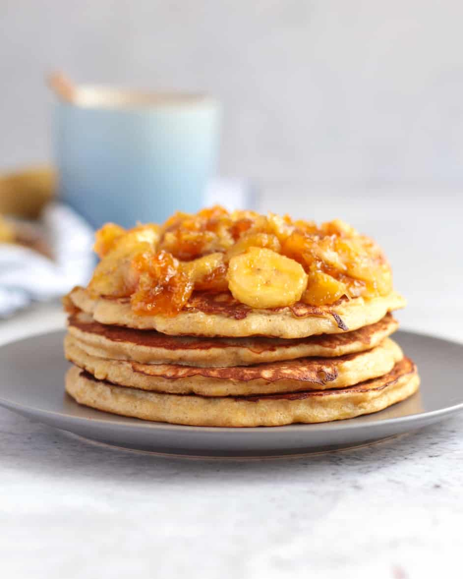 Stack of pancake topped with banana topping on a grey plate behind a white background.