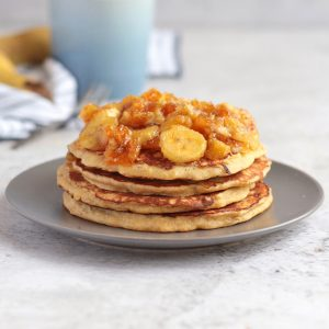 Banana Pancakes stacked on a grey plate and topped with honey caramelised bananas.