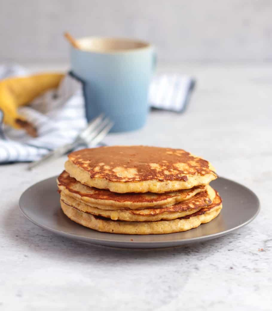 Four large pancakes on a grey plate behind a white background.