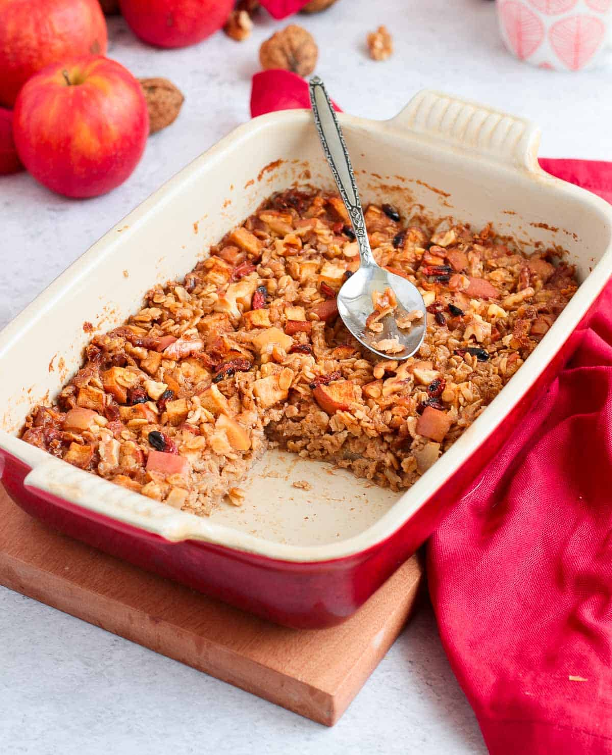 Baked Oatmeal in a white and red ceramic dish topped with a metallic spoon.