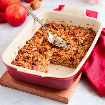 Baked Oatmeal in a white and red ceramic dish with a slice cut off.