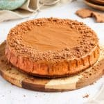 45' angle shot of the cheesecake on a round wooden board.