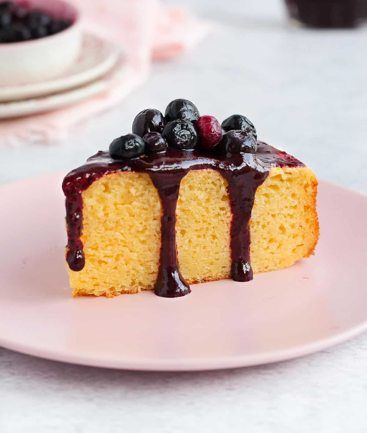 Blueberry topping poured over a slice of cake.