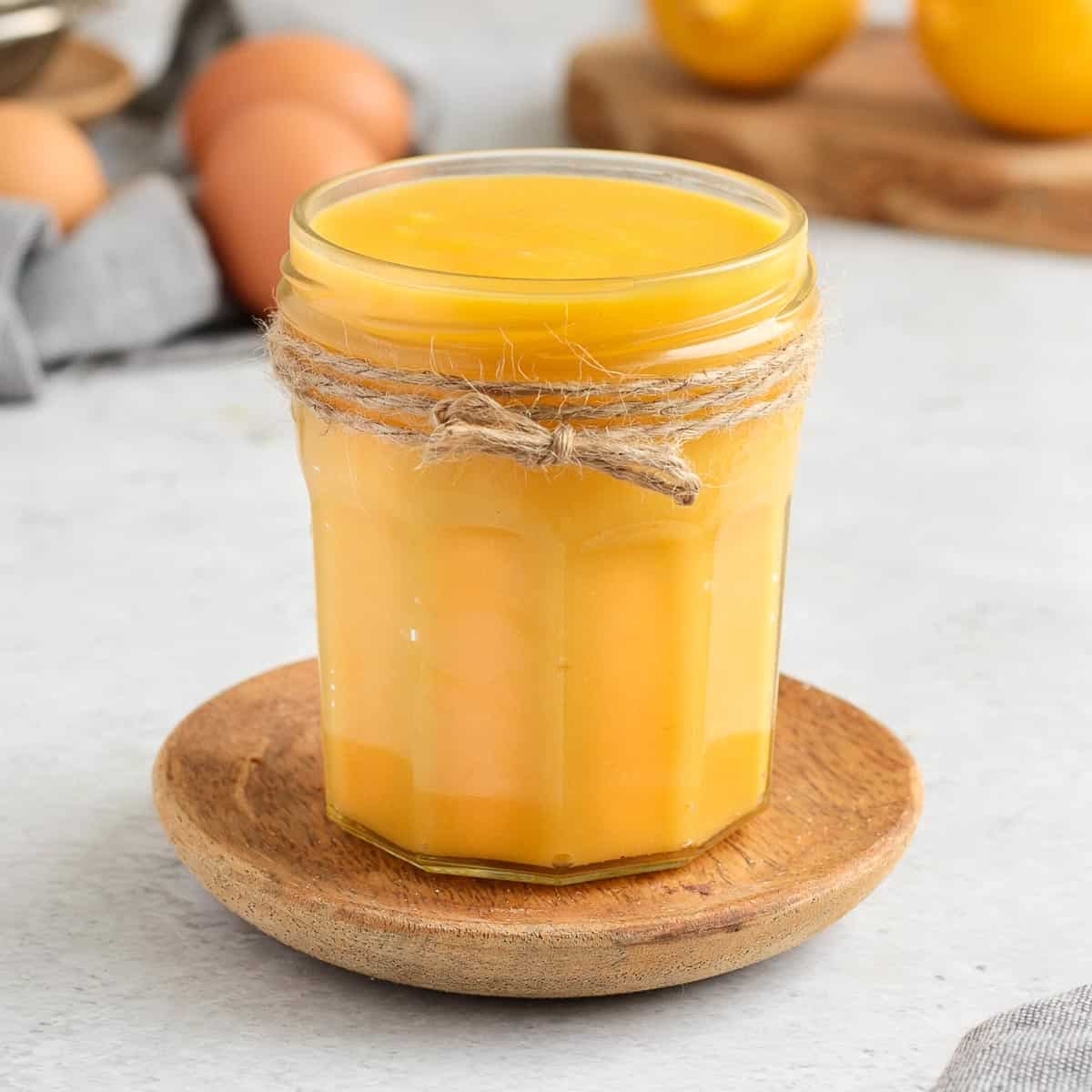 Lemon Curd in a glass jar over a small wooden plate.