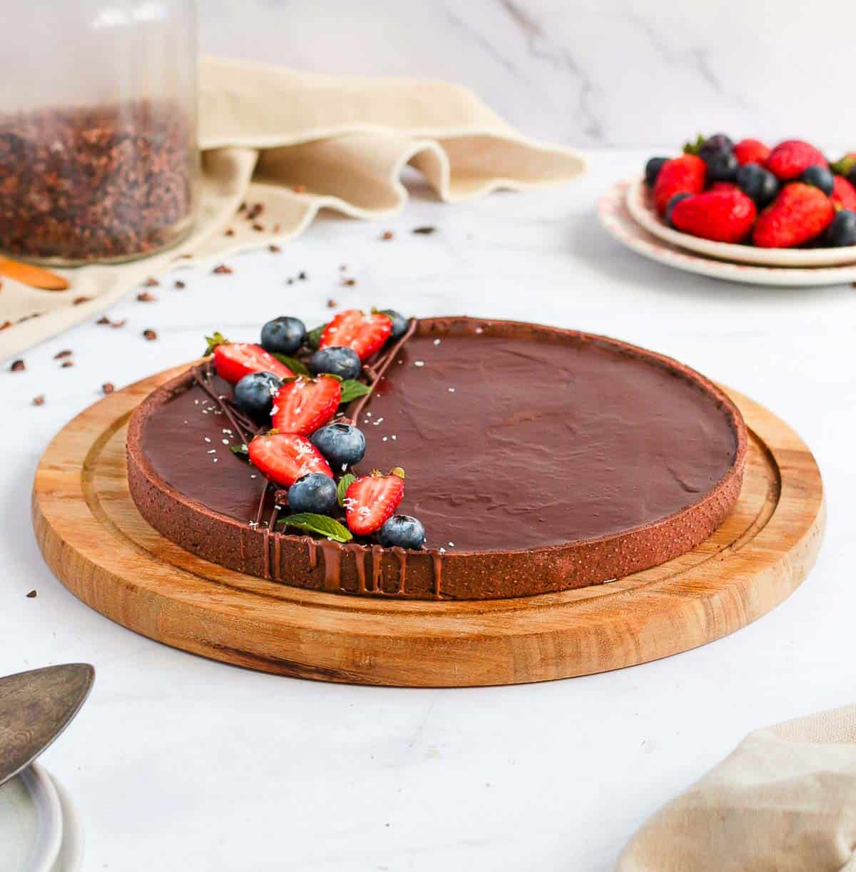 Tart on a round wooden board over a white surface.