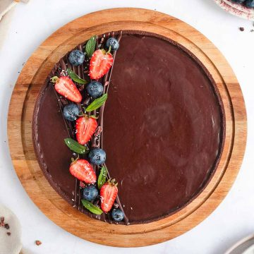 Chocolate Tart from above on a round wooden board.