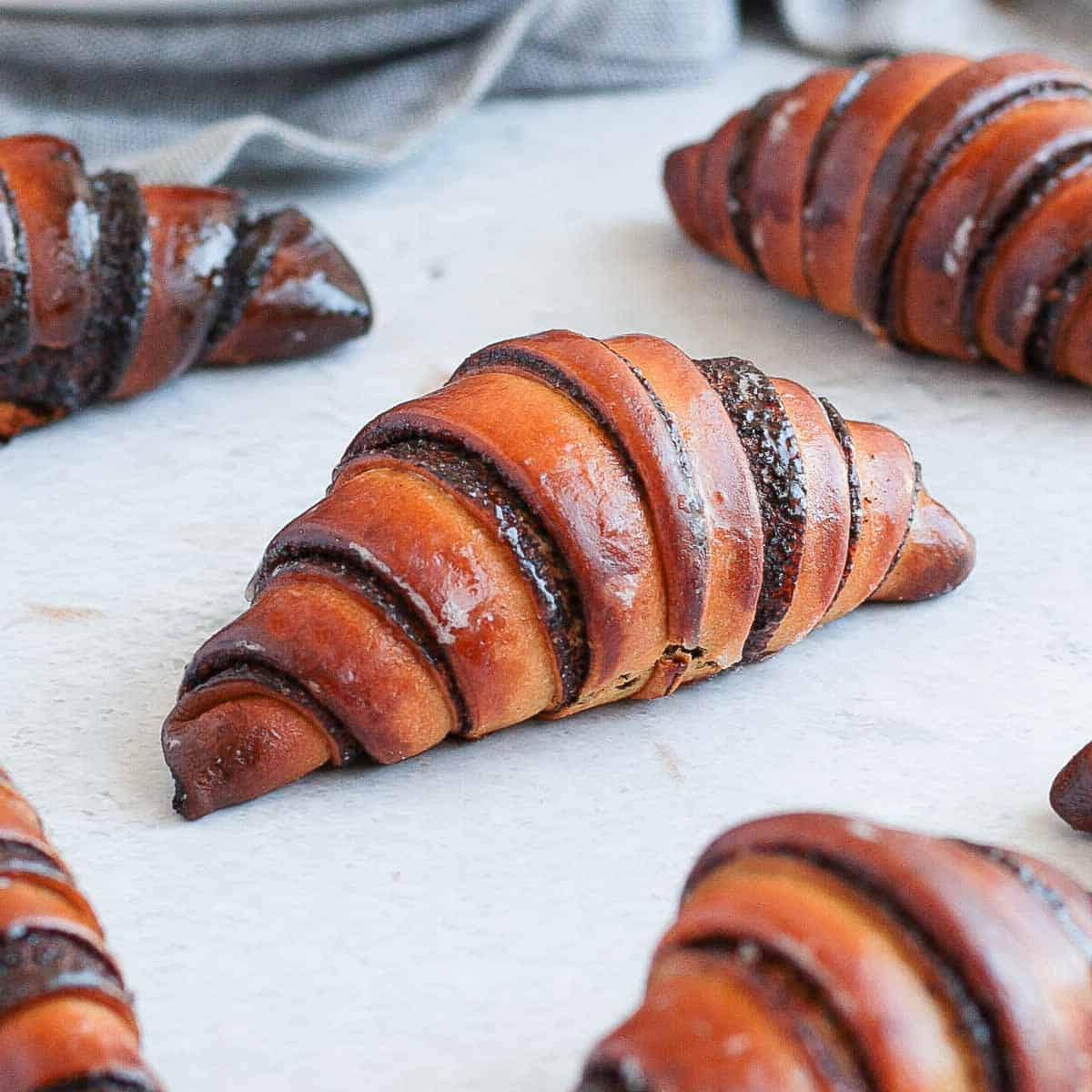 Close up on one chocolate rugelach on a grey surface.