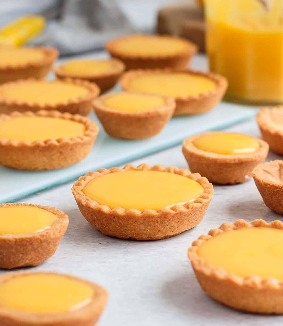 Finished lemon tarts on a grey surface.
