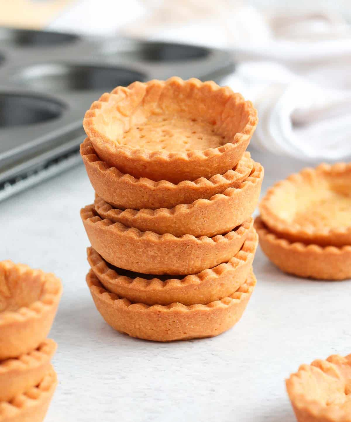 Mini tart shells stacked on a grey surface.